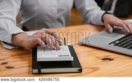 Businesswoman Using Calculator To Calculate The Numbers In The Company Financial Report. Famale Usin
