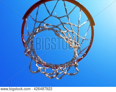 Basketball Hoop With A Net Against A Cloudless Blue Sky Under The Suns Rays. Closeup Photo From Bott