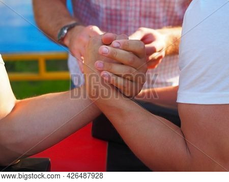 Male Muscular Arms In Outdoor Arm Wrestling Fight. Closeup Photo