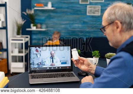 Senior Man Showing Doctor Pills Bottle At Webcam During Video Call. Elderly Man Discussing With Heal
