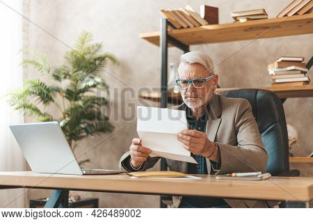 Late Payment, Court Notice. Surprised Mature Man Looking Through The Subpoena In The Office At The D