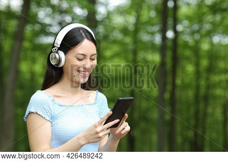 Korean Woman With Headphones Listening To Music Checking Smart Phone In A Forest