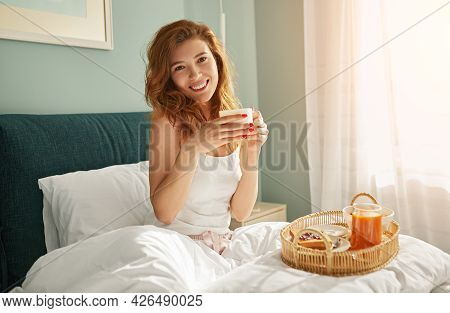 Optimistic Young Woman With Cup Of Hot Beverage Smiling And Looking At Camera While Sitting On Bed,