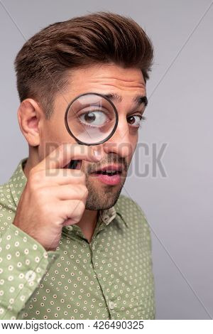 Inquisitive Young Guy In Dotted Shirt Looking At Camera Through Magnifying Glass While Searching For