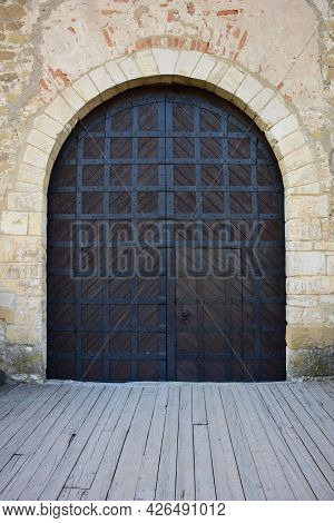 Wooden Gates Of An Old Medieval Castle Or Fortress, Covered With Strips Of Iron. The Gate Has A Clos