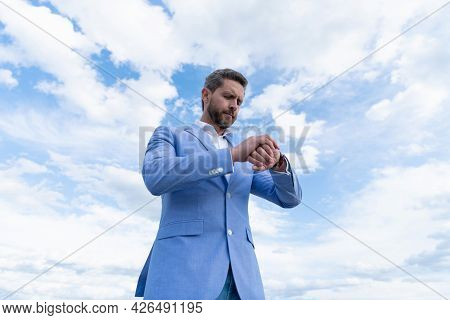 Handsome Mature Man Businessman In Suit Check Time On Wristwatch On Sky Background, Punctuality.