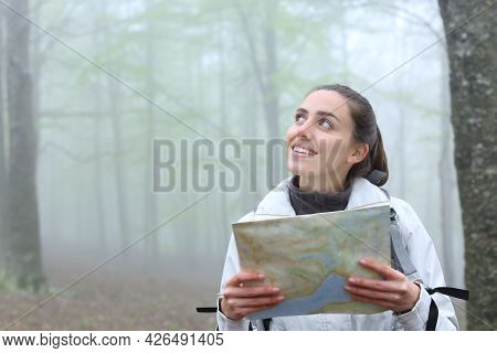 Happy Trekker Holding Paper Map Looking At Side In Nature A Foggy Day