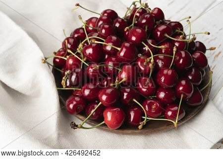 Wooden Bowl Of Organic Cherries On White Table, Linen Napkin With Wooden Bowl On A Table With Ripe S