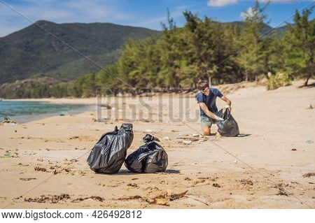 Man In Gloves Pick Up Plastic Bags That Pollute Sea. Problem Of Spilled Rubbish Trash Garbage On The
