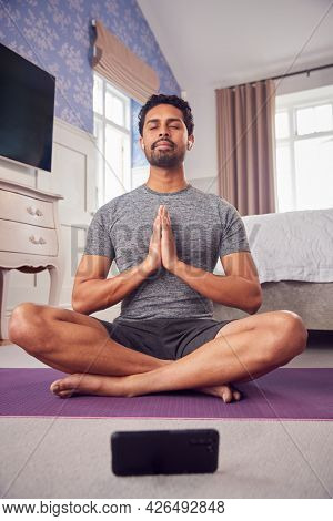 Man In Fitness Clothing In Bedroom At Home On Yoga Mat With Mobile Phone And Wireless Earphones