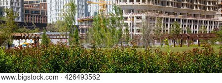 Residential Apartments Under Construction On The Background Of Green Leaves, Green Area In The City