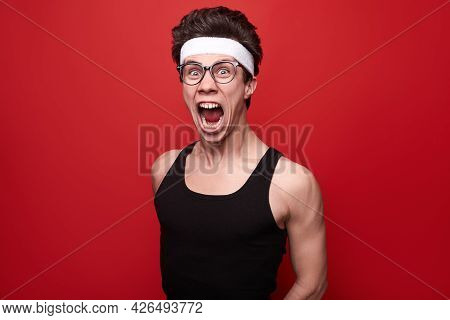 Funny Crazy Young Skinny Guy In Sports Outfit And Glasses Grimacing And Screaming Loudly During Fitn
