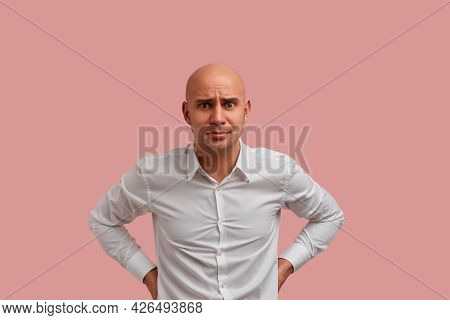 Disappointed Surprised Bald Man With Bristle Holds Arms In Akimbo And Frowns Eyes, Expresses Resentm