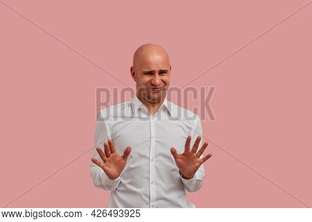 It Is Disgusting. Dissatisfied Bald Guy With Bristle Wears White Shirt Frowns Face In Dislike, Makes