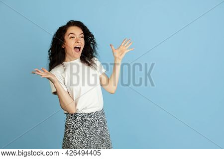 Wow, Astonished. Portrait Of Pretty Young Curly Caucasian Girl Isolated Over Light Blue Studio Backg