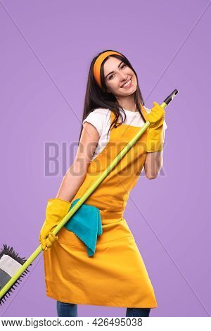 Optimistic Young Woman In Yellow Apron And Gloves Dancing With Mop During House Cleaning Routine Aga