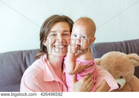 Unconditional Love. Portrait Of Young Woman Bonding With Her Newborn Baby, Sitting On Bed At Home