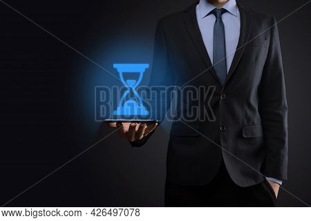 Businessman Man Holds In Hand Hourglasses Icon. Time Expires. A Reminder To Action. Business Concept