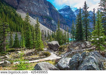 Surroundings of the mountain lake Moraine. Cloudy and cold autumn day. The magnificent Canadian Rockies are covered with glaciers. Travel to northern Canada.