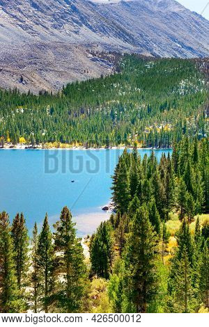 Magnificent oval lake with blue water is surrounded by picturesque mountains and coniferous forests. Rock Creek road lakes. Lush autumn in Montana, USA