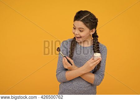 Look Here. Childhood Happiness. Smiling Child On Yellow Background. Applying Loose Powder With Brush