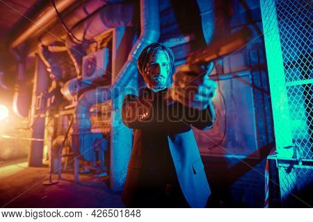 Mafia Wars. Portrait of a handsome wounded special agent standing on alert with a gun in his hand in backstreet of the night city.