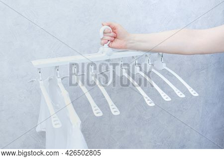 White Plastic Folding Clothes Hanger With Eight Hangers In The Hands Of A Caucasian Woman.