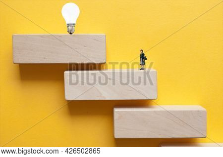 Miniature Woman On Steps Looking Towards Light Bulb Above