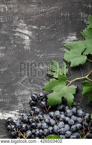 Black Grapes Food Frame. Black Juicy Grapes On Vintage Dark Concrete Background. Copy Space For Text