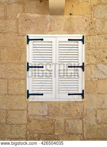 Window Closed Shutters On The Wall Of The House