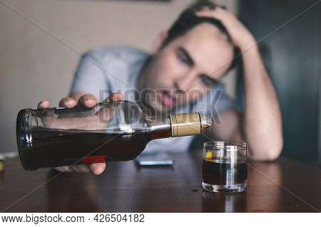 An Alcoholic Invokes A Strong Rum With A Glass Stack Lying On The Table. Of Strong Alcoholic Intoxic
