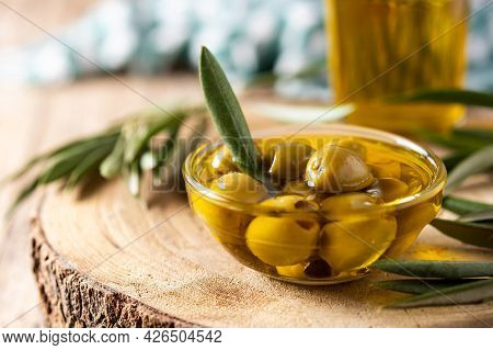 Virgin Olive With Green Olives In Crystal Bowl On Wooden Table