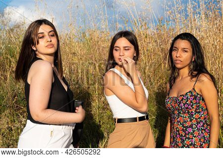 Three Models Well Dressed Posing With Tall Grass Behind