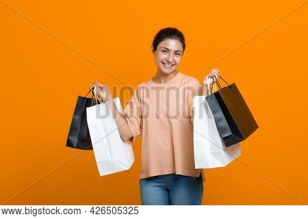 Indian Woman Holds Shopping Bags In Hands. Sale And Black Friday Concept