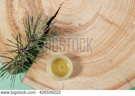 Natural Aromatherapy And Spa Concept - Small Glass Jar Of Essential Pine Oil, Branch, Wooden Saw Cut