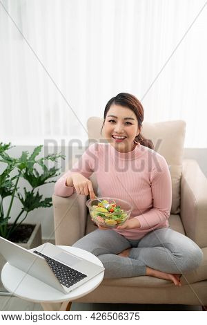 Young Adult Asian Woman Eating Salad And Using Laptop Computer For Watching Online Movie On Internet