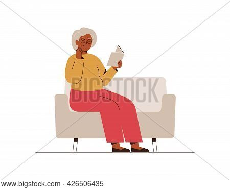 Senior Woman Sits On The Couch And Reads The Book With Interest. Grandmother Spends Time At Home Wit
