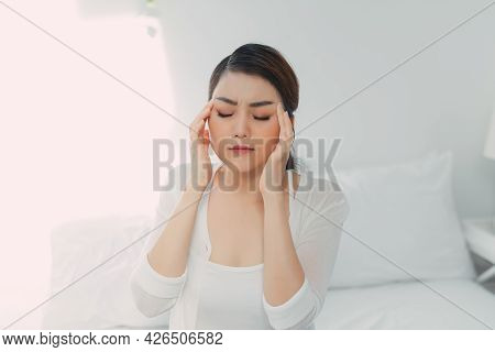 Young Woman With Headache, She Is Sitting On The Bed And Touching Her Temples