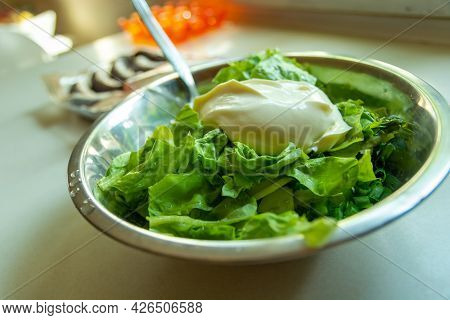 Rinsed Green Lettuce With Sour Cream In A Bowl