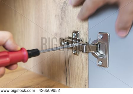 Concept Of Home Repairing. A Hand Of A Furniture Assembler Adjusting A Mechanism For Opening The Doo