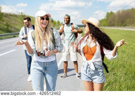 Group Of Multinational Millennial Friends Walking Along Highway, Chatting To Each Other, Laughing, H