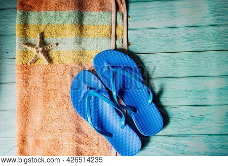Beach Items On Wood Background. Summer Concept - Towel And Flip Flops