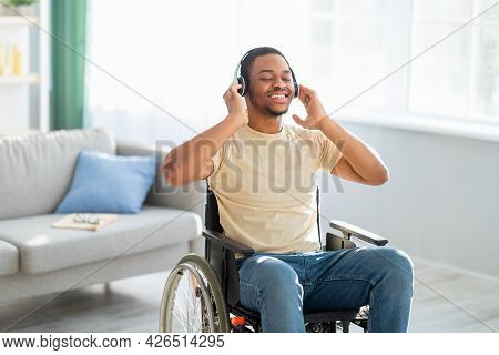 Joyful Impaired Black Guy In Wheelchair Listening To Music, Using Headphones At Home, Copy Space