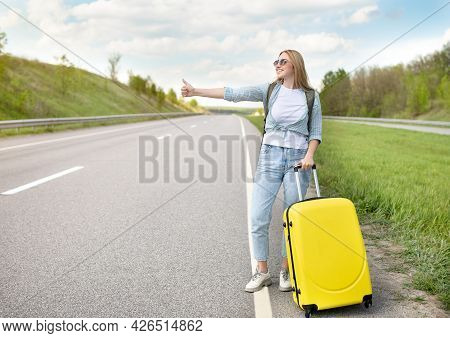 Young Blonde Lady With Backpack And Suitcase Hitching Ride, Stopping Passing Car, Standing On Roadsi