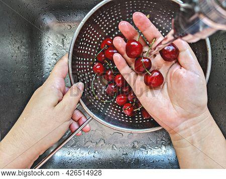 Ripe Fresh Cherries Berry In Steel Sieve Is Hand Washed Under Tap Water In Sink