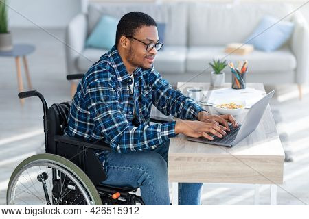 Online Work For Disabled People. Handicapped Black Guy In Wheelchair Using Laptop For Remote Job At