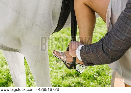 A Man Helps A Girl Put Her Foot On A Ladder And Climb A White Horse.