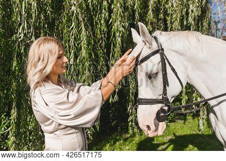 Belarus, Minsk Region - September 20, 2020: Attractive Blonde European Appearance Strokes A White Ho