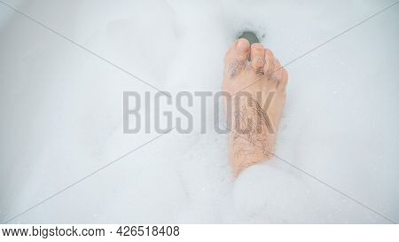 Funny Picture Of A Man Taking A Relaxing Bath. Close-up Of Male Feet In A Bubble Bath