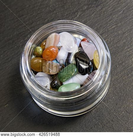 Collection Of Semi-precious Gemstones In Small Glass Jar On Black Slate Knitted Background Close Up